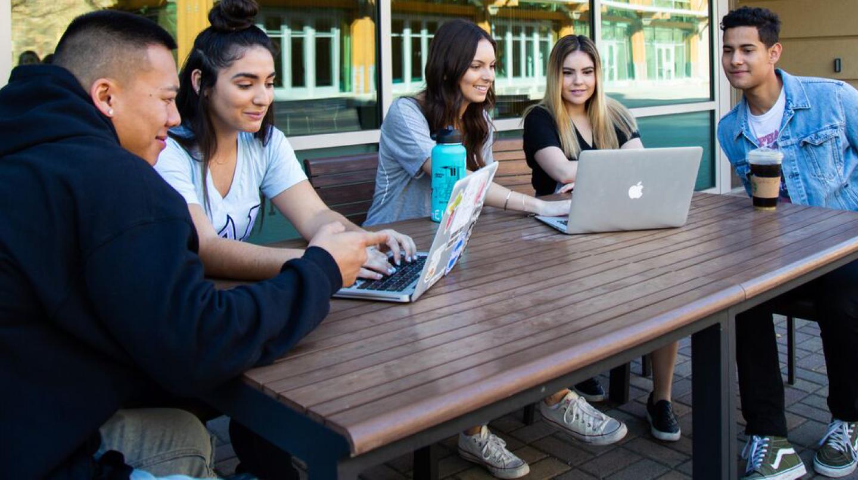 students on laptops reading